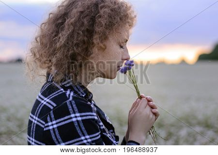 The girl sniffs a bouquet of cornflowers against the background of the evening sky and a flower field