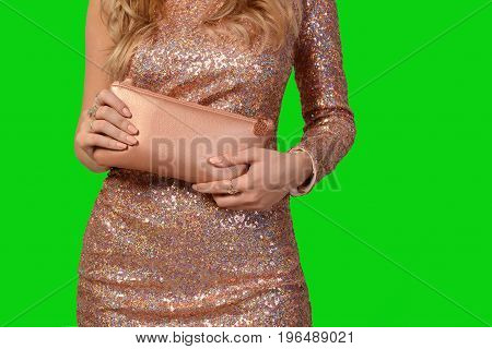 Woman in pink dress with sequins holds a clutch in hands on a green background.
