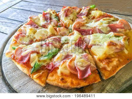 Hawaiian pizza on the old wood table