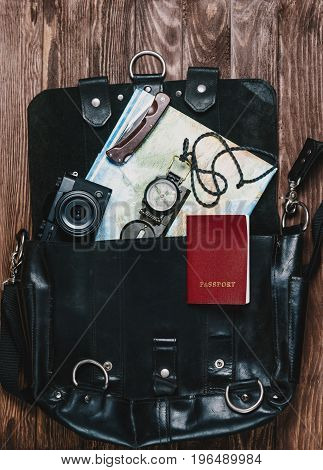 Travel objects in a suitcase on wooden background top view.