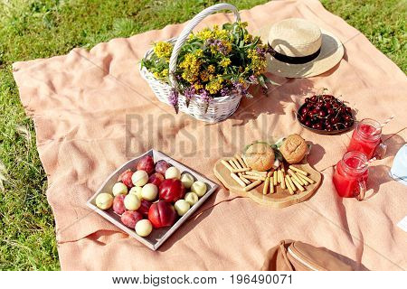 Picnic at the park on the grass: tablecloth, basket, healthy food and accessories