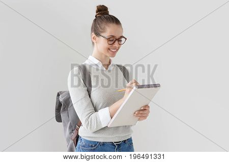 Beautiful Student Girl Turned Rightwards On Grey Background Looking At Page Of Notebook And Writing