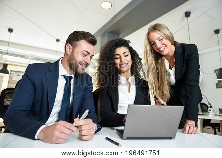 Multi-ethnic Group Of Three Businesspeople Meeting In A Modern Office.