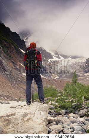 Man Adventurer Looks At The Glacier Lying In Front Of Him