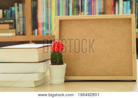Wooden picture frame on desk next to stack of books and behind a small red cactus flower.