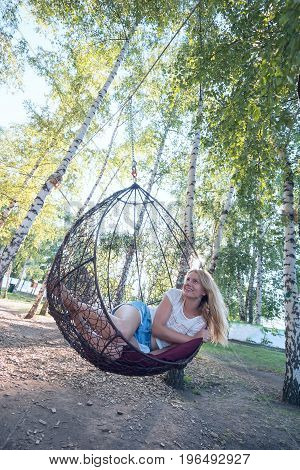 Romantic Young Woman Riding On A Hanging Chair