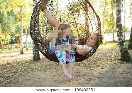Beautiful Young Mom And A Funny Little Daughter Are Relaxing On A Hanging Chair