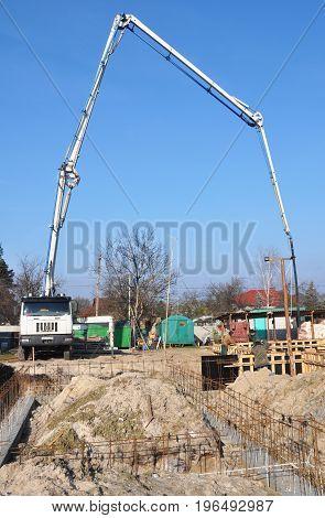 KYIV UKRAINE - AUGUST 16, 2017: Building a Foundation. Contractors making a concrete slab house foundation with car with pump tube. Pouring a concrete slab along the foundation