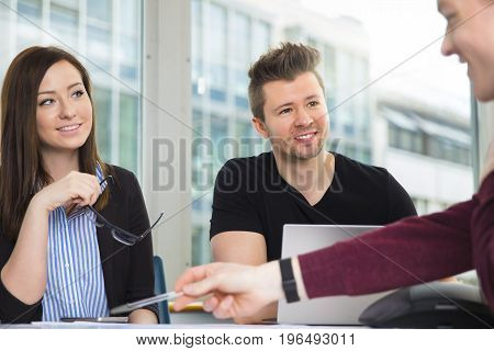 Smiling male and female business people looking at colleague explaining at desk in office