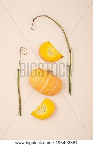Fresh Orange Cut Pumpkin And Dried Branches On A Light Beige Pastel Background Close-up..