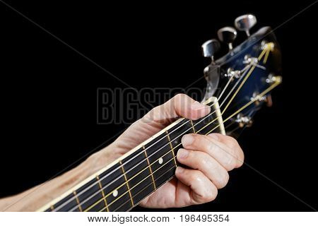 Man playing on acoustic guitar. Closeup fingers on guitar neck. Isolated on black. Shallow focus.