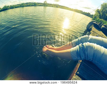 girl in blue jeans sits on the old wharf in the lake on a sunny day. Caucasian.