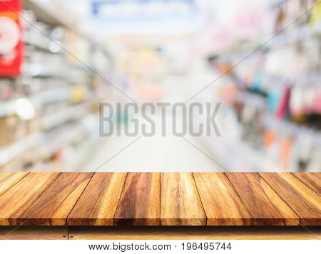 Empty top of wood table on blur supermarket background.