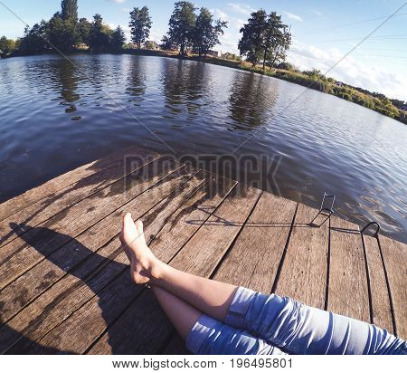 girl in blue jeans sits on the old wharf in the lake on a sunny day