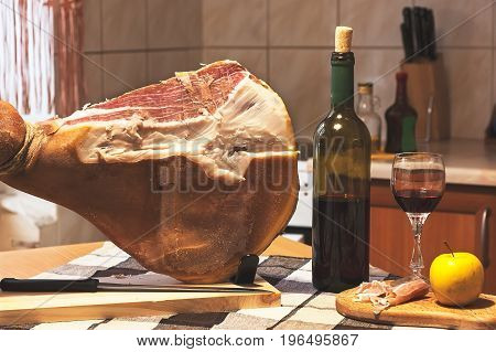 Spanish Jamon Serrano, tabla jamonera, jamonero knife with glass and bottle of wine. Food photo concept
