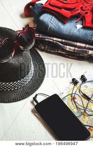 Travel accessories: hipster sneakers, denim shorts, plaid shirt, cowboy belt, hat, sungkasses, map and phone with headphones on wooden background. Selective focus. Traveling concept