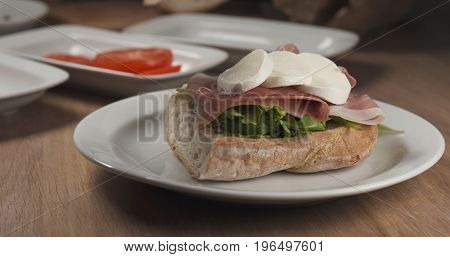 making italian sandwich with speck and mozzarella apply cheese, wide photo