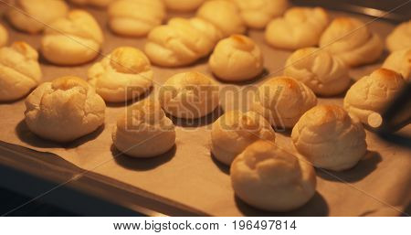 cooking profiteroles in oven closeup, wide photo