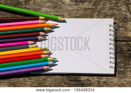 Colored Pencils And Blank Notepad On Old Wooden Desk