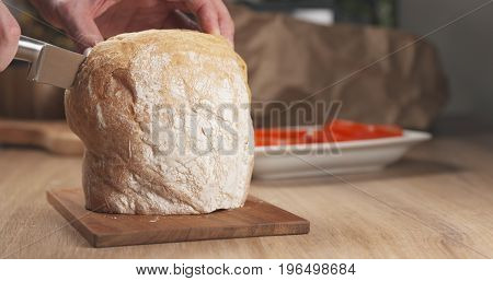 young man hands slicing ciabatta on cutting board, wide photo