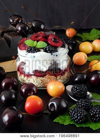 Oatmeal with yogurt and berries in a jar surrounded by cherries and blackberries. Layered breakfast
