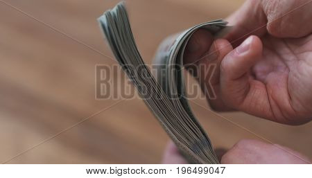 closeup man hands flipping dollars, wide photo