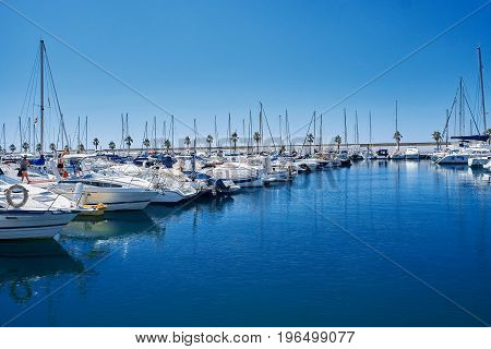 Yacht harbor in blue sunset light, luxury summer cruise, leisure time, active life, vacation and holidays concept Yachts and their reflection in the city's port