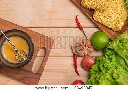 Instant Noodles For Cooking And Eat In The Dish With Whipped Egg And Vegetables On Wooden Background