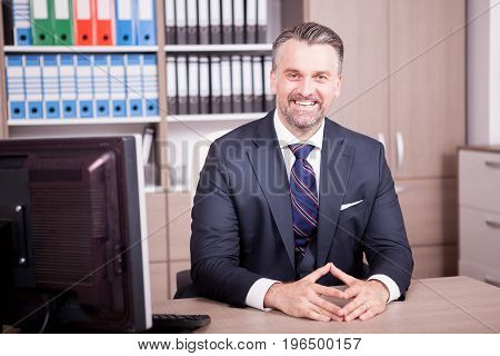 Smiling adult CEO at his desk in office. Business and corporate. Confident CEO