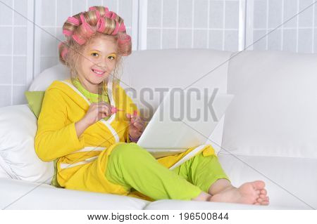 cute little girl with laptop polishing nails