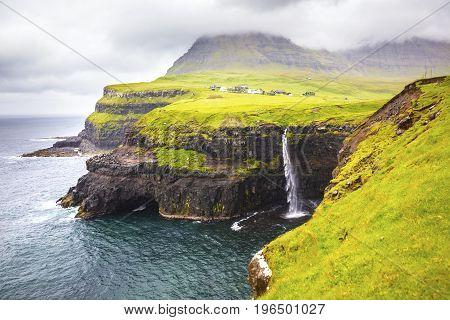 Dramatic waterfall in rainy weather on Faroe Islands and the village Gasadalur in the background.