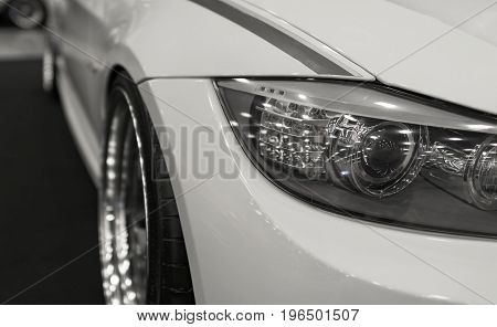 Headlight of a modern sport car.The front lights of the car and alloy wheel. Modern Car exterior details