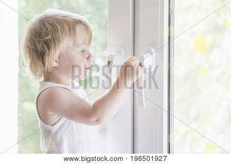 Child opens the window. Little girl on window. The window is locked to the castle from the children.
