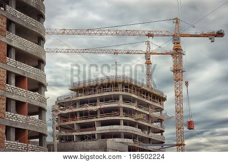 Industrial construction close-up. Construction cranes against background of concrete walls of new buildings. Concept of construction. Construction site.
