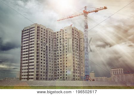 Construction crane builds multi-apartment residential house. Construction of residential house with crane. New housing concept construction.