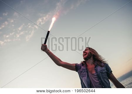 Handsome young man with long hair is taking red coloured fire in hand and smiling.