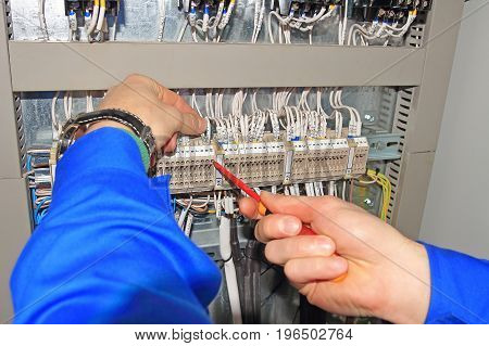 Engineer clamps electrical wires into terminals of electrical cabinet with screwdriver. Electric Power Concept. Hands electric closeup