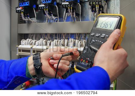 Electrician measures voltage with multimeter in  electrical cabinet. Adjustment of the electrical circuit by an electrician.