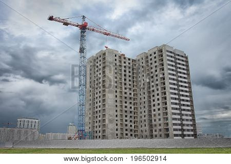Construction of a new multi-apartment residential building. Construction crane near  house under construction on construction site.