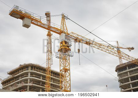 Construction crane builds new concrete shopping center buildings on construction site. Construction of new real estate. Concept of construction.