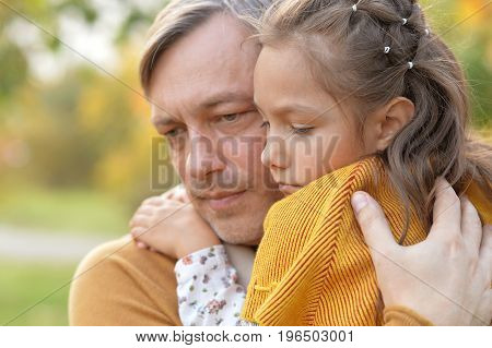 Portrait of father and daughter hugging outdoors
