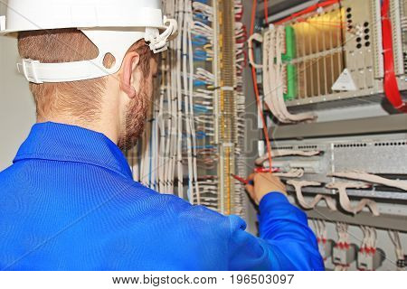Electrician in white helmet is repairing broken power equipment. Adjustment of electrical equipment by a professional engineer.