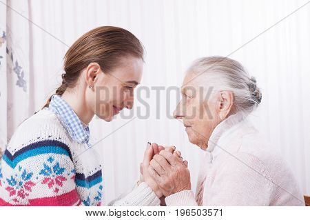 Senior and caregiver holding hands at home closeup