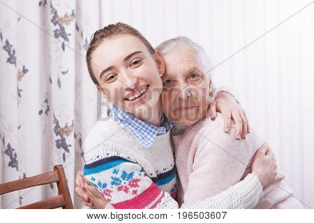 Helping hands, care for the elderly concept closeup. Senior and caregiver holding hands at home