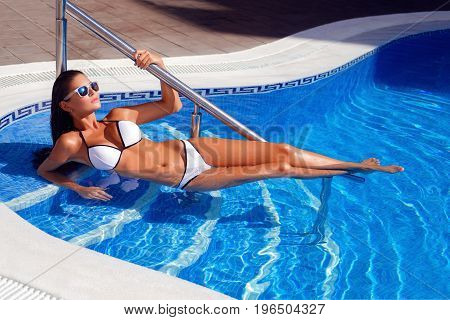 Beautiful tanned young woman with perfect body wearing white bikini and sunglasses relaxing in swimming pool. outdoor shot. copy space.
