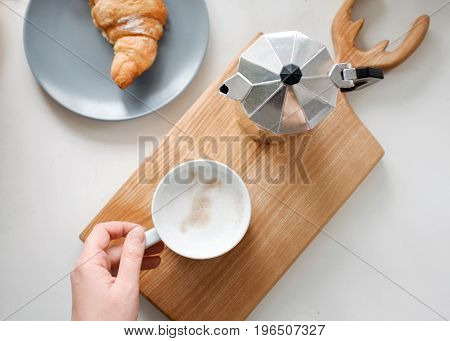 A cup of tea in his hand, a croissant and a coffee pot on the table. view from above
