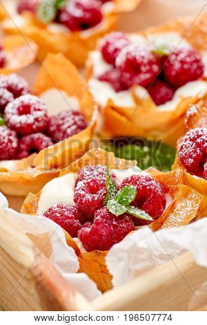 Phyllo cups with Mascarpone cheese  filling topped with fresh raspberries and mint, delicious dessert