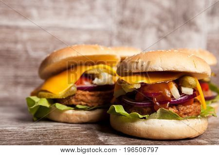 Delicious home made snack burgers on wooden plate. Fast food. Unhealthy snack