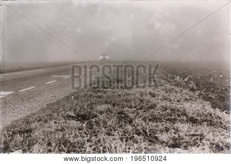 Old black and white photo of car with headlights driving on misty rural road.