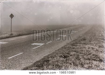 Old black and white photo of rural road with traffic sign in dense mist.